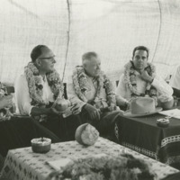 Photograph of the Congressional Delegation inside a tent wearing garlands<br /><br />