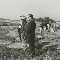 Photograph of Congressmen Poage and Dole wearing garlands in a paddy field<br /><br />