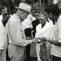 Photograph of Congressman Poage presenting Kennedy half-dollar to Hindu holy man<br /><br />