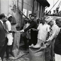 Photograph of Congressmen Poage and Dole watching the unloading of American food grain<br /><br />